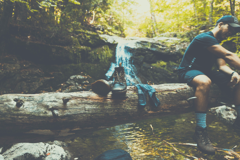 hiker drying his socks and shoes while sitting on a log across a stream