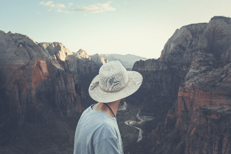 man wearing wide brimmed hat looking down canyon