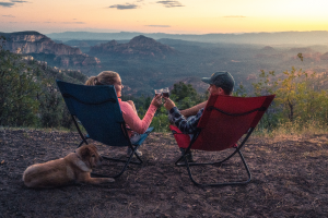 couple sitting in camping chairs drinking wine with a view