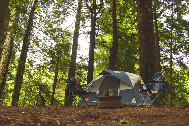 two camping chairs standing beside blue tent in woods