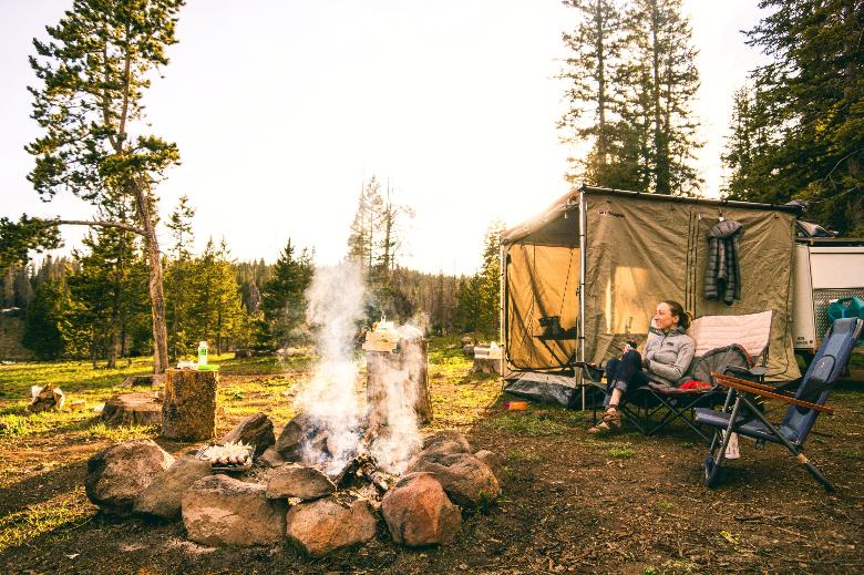 woman sitting beside a campfire and tent during the day