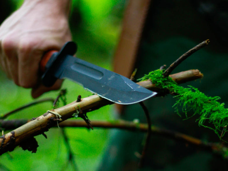 person using full tang knife to strip branch of twigs