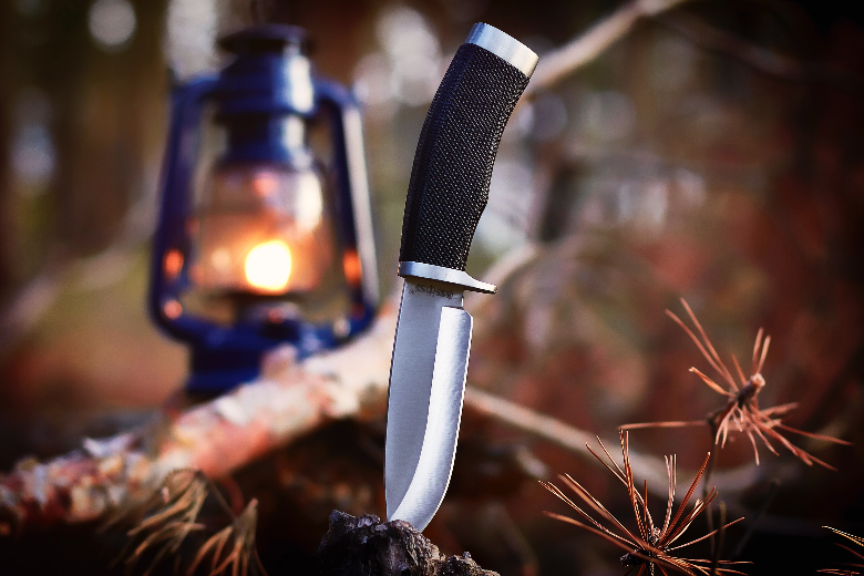 fixed blade stainless stuck in stump lamp in background