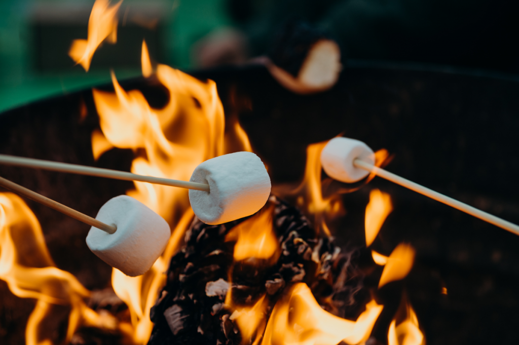 three marshmallows roasting over a campfire
