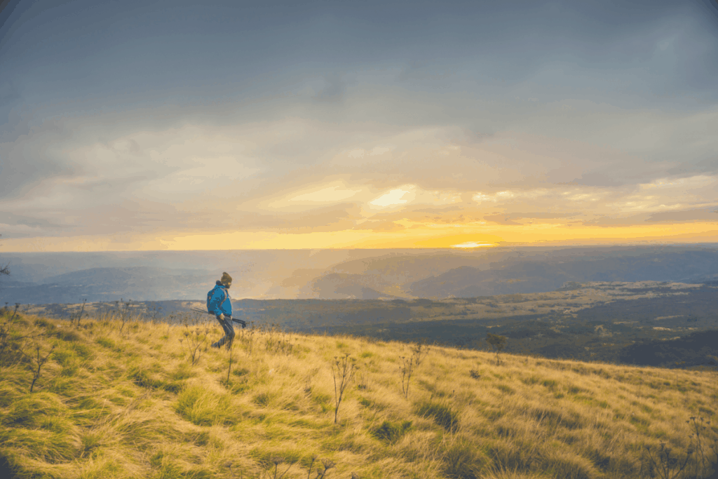 man hiking through a field on a mountain with the sun shining through clouds