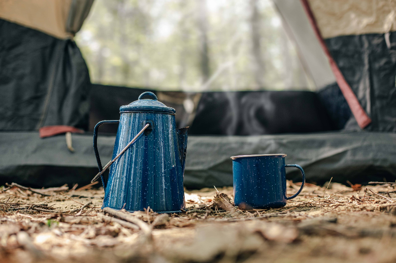 blue kettle and cup in front of tent