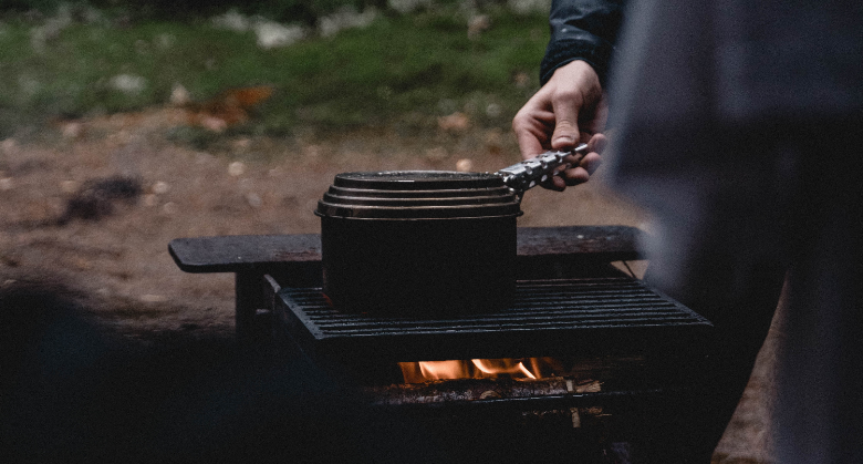 pot heating on grill over wood fire as man holds handle
