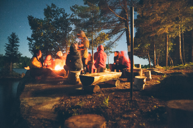 group of campers eating around campfire at dusk