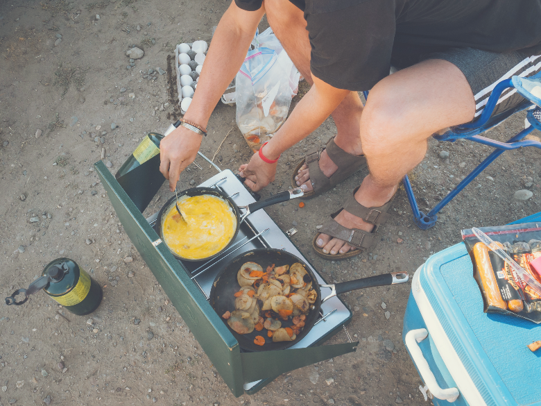 person cooking meal on camping stove