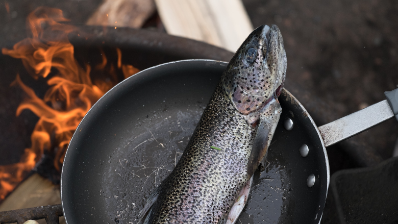 trout in frying pan in preparation for being cooked