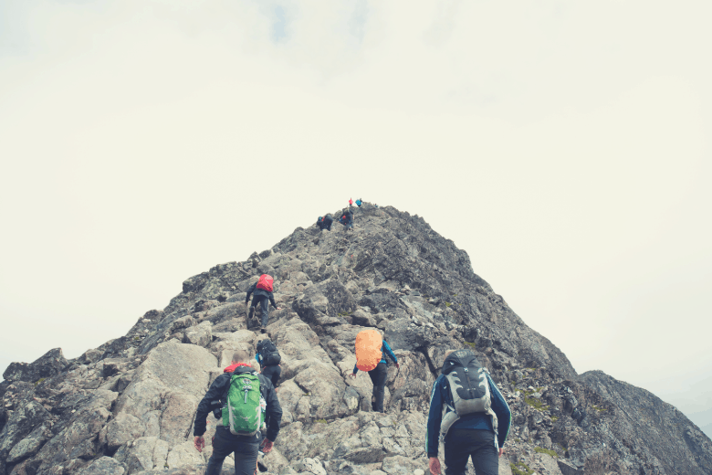 group of hikers climbing up boulders on side of mountain