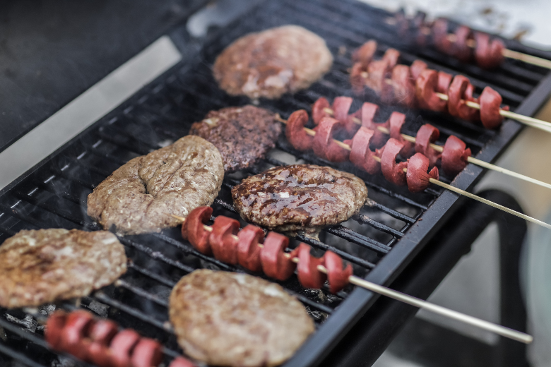 skewered hotdogs and burger patties cooking on a grill