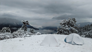 two tents covered in snow on mountaintop