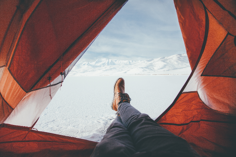 person looking out from inside a red tent with feet in the snow