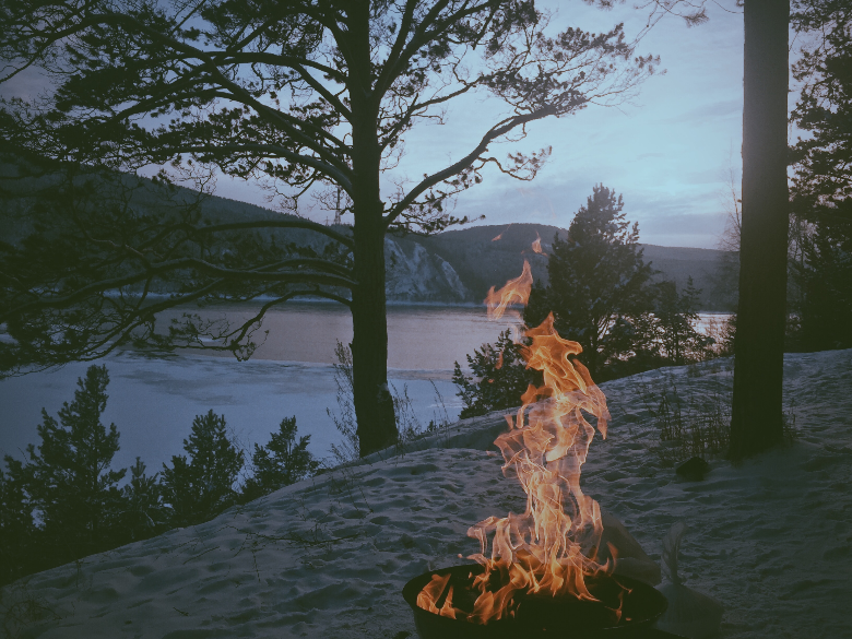campfire in the winter overlooking a frozen lake