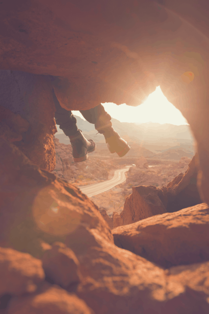 man sitting on rock with feet hanging over edge in golden hour