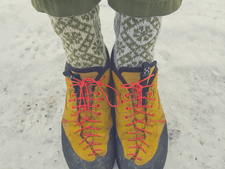 person wearing yellow shoes with red laces and wool socks