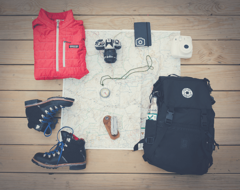 collection of gear camera shoes pack compass jacket on map