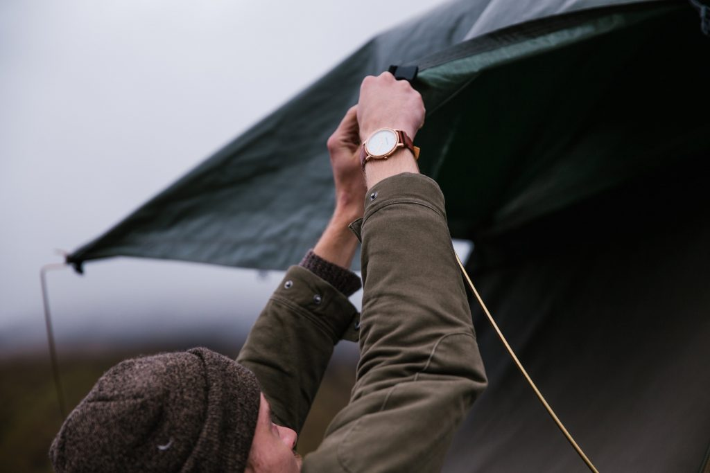 man securing the side of a tent during setup