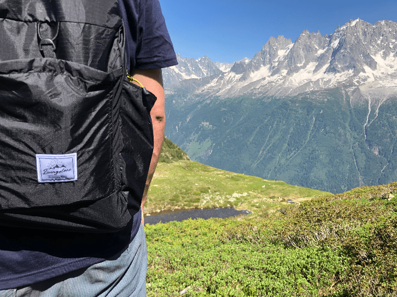 person wearing backpack with mountains beyond