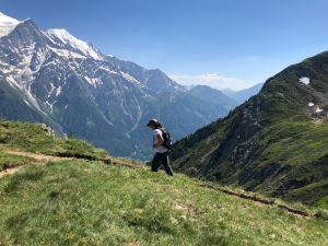 woman climbing trail with Alps beyond