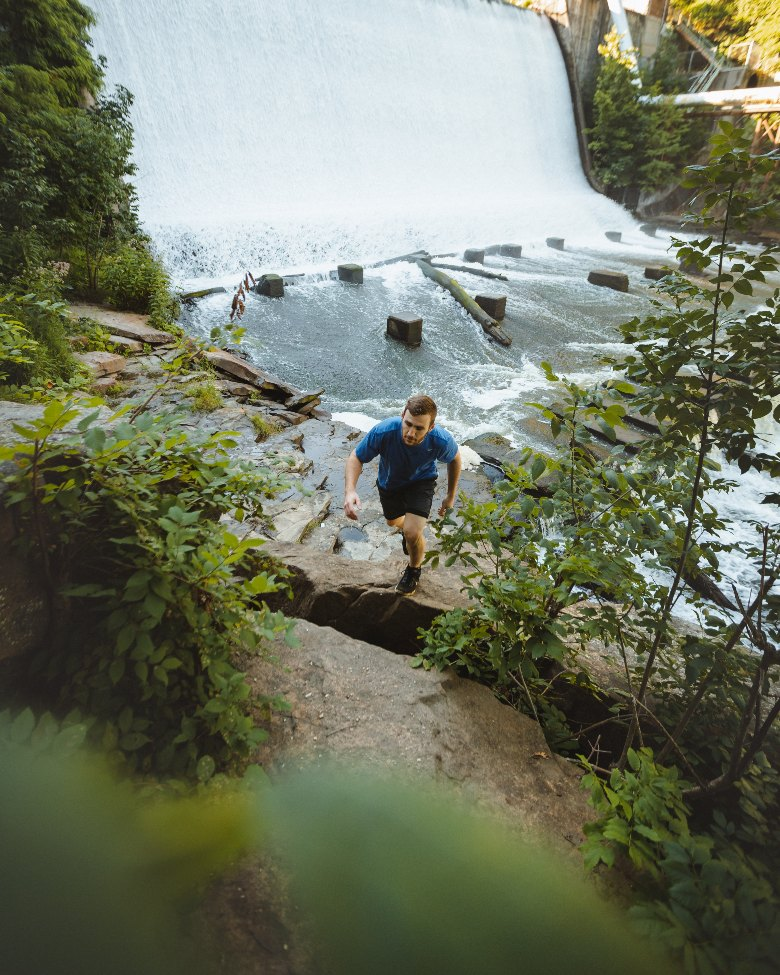 man climbing steep rocky trail next to a large dam waterfall