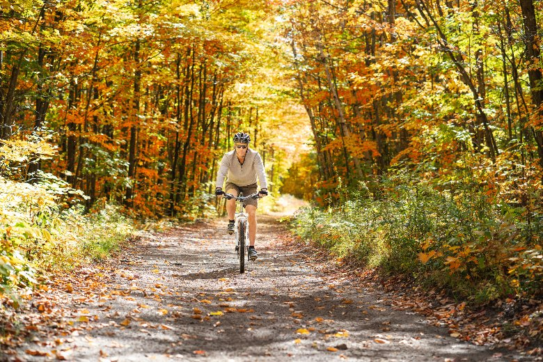 man biking down trail in the autumn wearing a helmet
