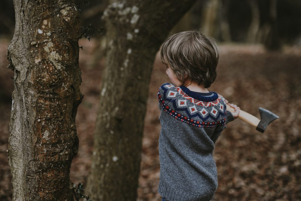 young boy swinging hatchet at a tree