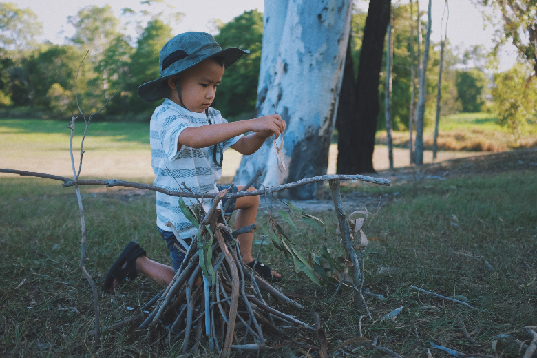 young boy with hat preparing sticks for a fire in the grass