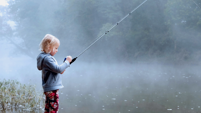 young girl with blond hair standing with fishing pole by a still river