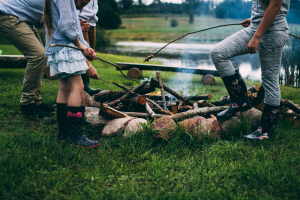 children standing in uncut grassroasting marshmallows over a campfire