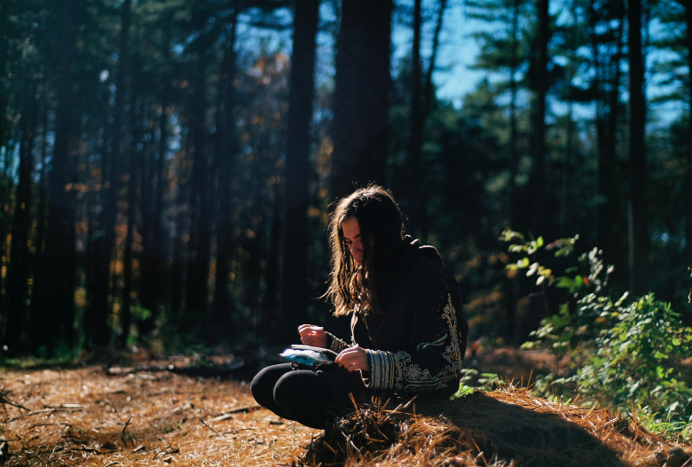 young woman journaling while sitting on a fallen log in the woods