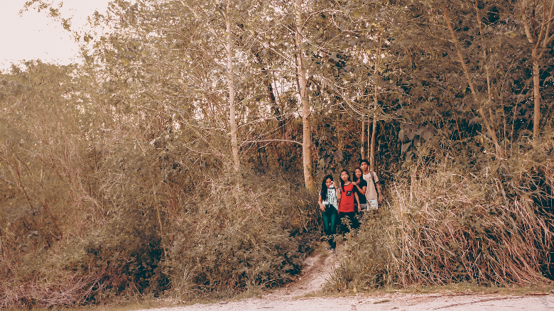 group of young teenagers emerging from a trail through the woods