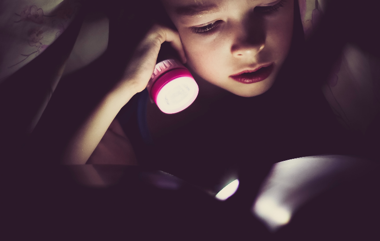 boy reading a book in the dark using a flashlight