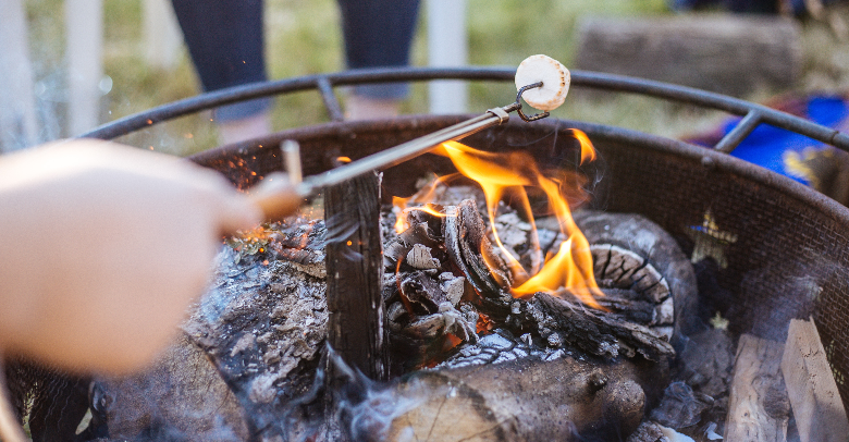 someone roasting a marshmallow over a fire pit in the daytime