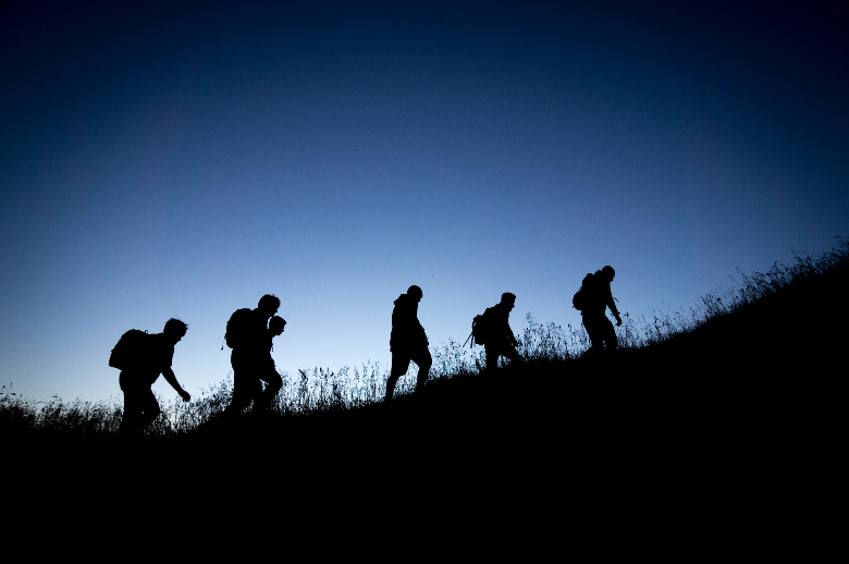 silhouettes of of a group of hikers climbing a ridge
