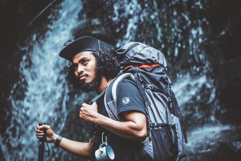 man wearing backpack and hat standing in front of waterfall