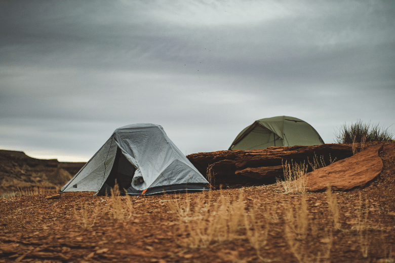 two tents on prairie and large flat rocks gray sky and sparse brown grass