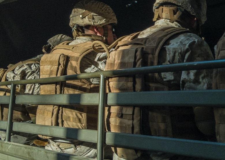 soldiers with backpacks sitting against rail of a truck
