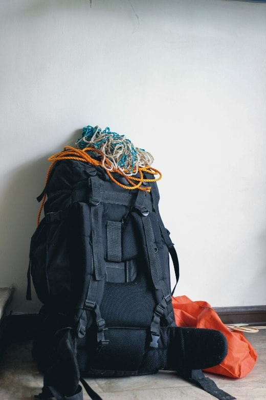 black backpack sitting on floor against white wall with rope