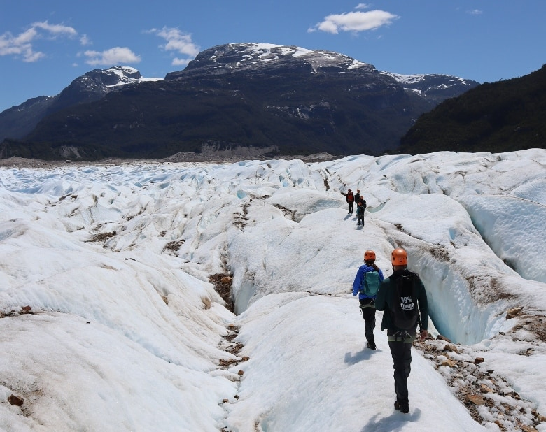 people walking across a glacier