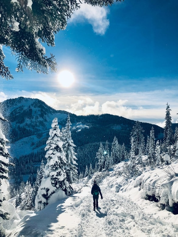 person walking down a mountain covered in snow sun shining
